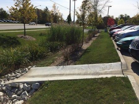 Curb cut in parking lot to a rain garden